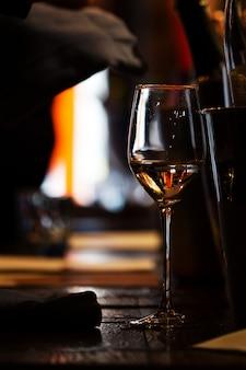 Ein glas wein auf dem holztisch des restaurants.