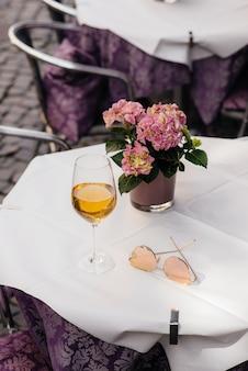 Ein glas wein auf dem tisch eines schönen coffeeshops mitten in europa. sich ausruhen