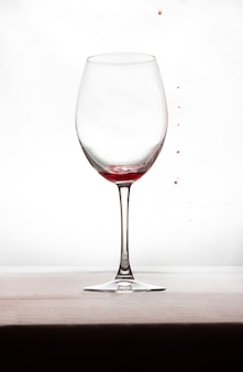 Ein glas wein mit etwas wein und ein paar tropfen rot außen
