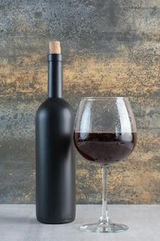 Ein glas wein mit flasche auf weißem hintergrund. foto in hoher qualität