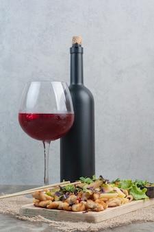 Ein glas wein mit flasche und leckeren makkaroni auf sackleinen.