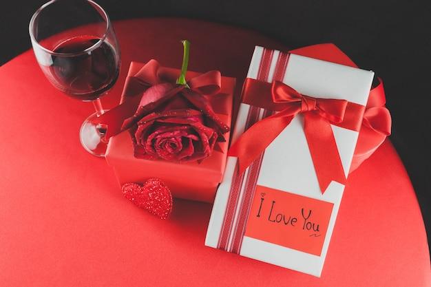 Ein glas wein mit geschenken und eine rose auf einem roten tisch
