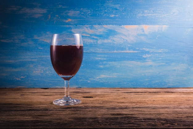 Ein glas weine auf einem holztisch. rote weine mit fleischgerichten