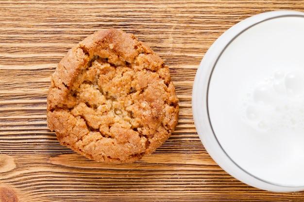 Ein glas weiße frische milch und knusprige hausgemachte kekse auf dem tisch, küche kochen
