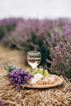 Ein glas weißwein, käse, trauben, biscotti und ein blumenstrauß auf einem heuhaufen zwischen lavendelbüschen. romantisches picknick. weicher selektiver fokus.