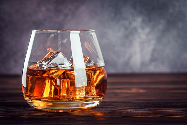 Ein glas whisky auf dem dunkelbraunen holztisch. transparentes gelbes alkoholisches getränk mit eis. brandy, bourbon. starkes alkoholisches getränk. kopieren sie platz für text, vorlage.