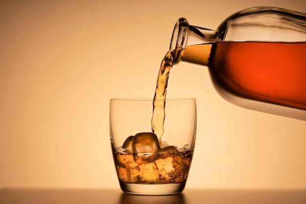 Ein glas whisky auf den felsen. bourbon oder cognac aus einer schnapsflasche gießen.