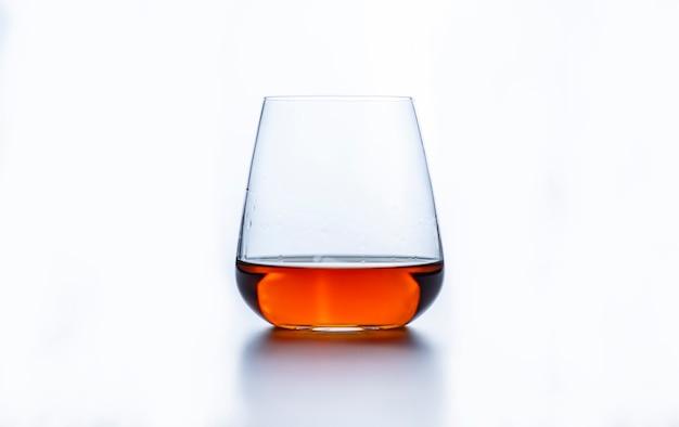 Ein glas whisky auf einer weißen oberfläche