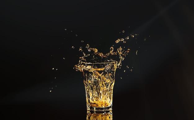 Ein glas whisky mit spritzern aus dem eiswürfel über dem schwarzen raum. alkohol spritzt. whisky oder cognac oder eine andere art von alkohol mit spritzern.