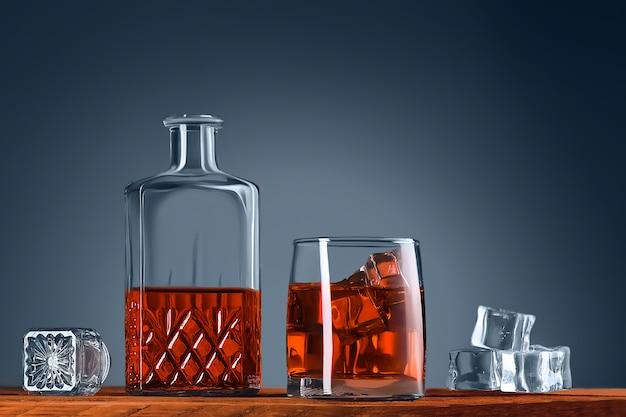 Ein glas whisky oder cognac, eine karaffe und eiswürfel