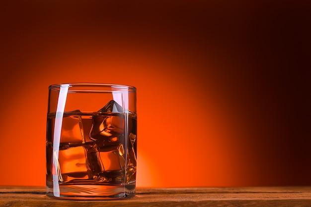 Ein glas whisky oder cognac und eiswürfel.