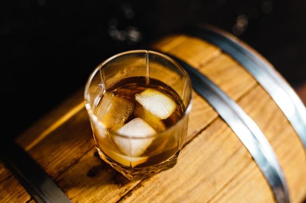 Ein glas whisky sitzt auf einem holzfass