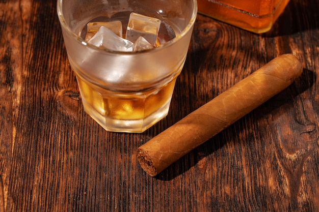 Ein glas whisky und zigarre auf holztisch