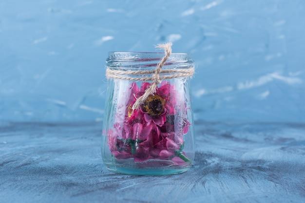 Ein glasgefäß mit künstlichen lila blüten auf blau.