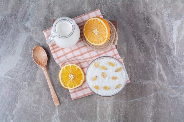 Ein glaskrug milch mit gesundem haferbrei und geschnittenen orangenfrüchten.