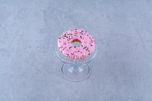 Ein glasteller mit cremigen süßen donuts mit bunten streuseln.