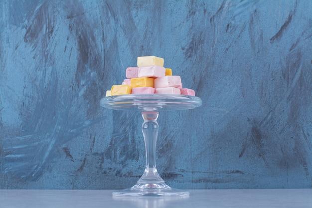 Ein glasteller mit rosa und gelben süßen süßwaren pastila