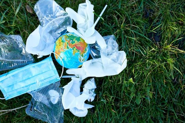 Ein globus in einem haufen verstreuten mülls auf einem grünen gras