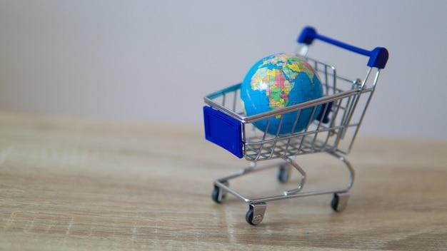Ein globus und ein tablet im globalen marktkonzept des einkaufswagens.