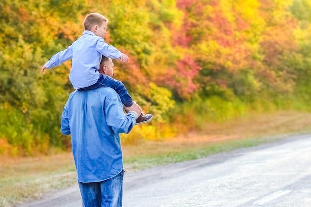 Ein glücklicher elternteil mit einem kind im park hände auf naturreisen gehen die straße entlang