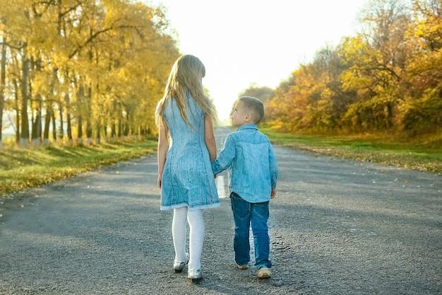 Ein glücklicher elternteil mit kind geht die straße entlang im park auf naturreisen
