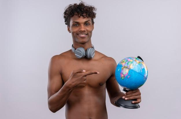 Ein glücklicher ernsthafter junger hübscher dunkelhäutiger mann mit lockigem haar, der kopfhörer trägt, die mit zeigefinger auf globus zeigen