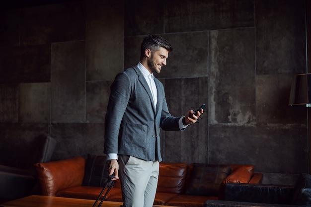 Ein glücklicher geschäftsmann, der sein gepäck trägt, während er den hotelflur entlang geht und sein telefon benutzt.