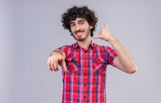 Ein glücklicher gutaussehender mann mit lockigem haar im karierten hemd, das hand nahe ohr hält, gestikuliert telefonzeichen mit den fingern