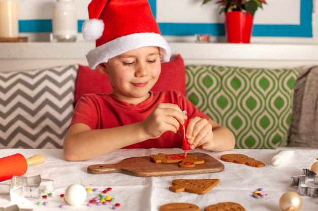 Ein glücklicher junge in einem weihnachtsmann-hut schmückt ingwerplätzchen in der küchenweihnachtsbeleuchtung