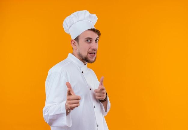 Ein glücklicher junger bärtiger kochmann in der weißen uniform, die mit zeigefingern auf eine orange wand zeigt