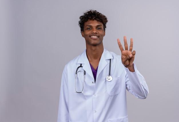 Ein glücklicher junger gutaussehender dunkelhäutiger arzt mit lockigem haar, der einen weißen kittel mit stethoskop trägt und nummer drei mit den fingern zeigt