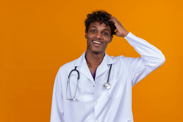 Ein glücklicher junger gutaussehender dunkelhäutiger mann mit lockigem haar, der weißen mantel mit stethoskop trägt, das hand auf kopf hält