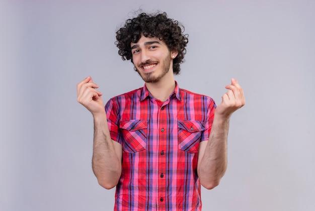 Ein glücklicher junger hübscher mann mit dem lockigen haar im karierten hemd, das geldgeste zeigt