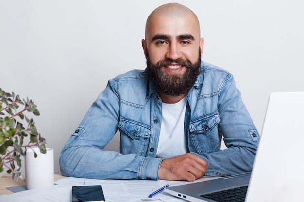 Ein glücklicher junger kahlköpfiger geschäftsmann, der dicken dunklen bart in jeanshemd gekleidet am tisch in seinem büro mit laptop sitzt