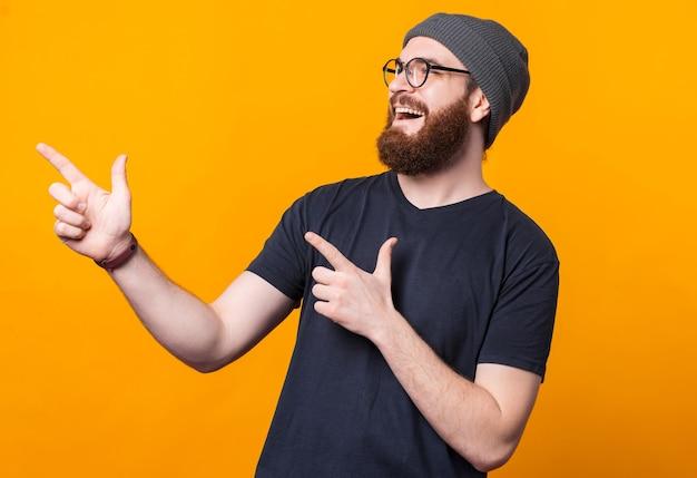 Ein glücklicher junger mann mit bart lächelt und zeigt mit seinen fingern auf eine freie stelle