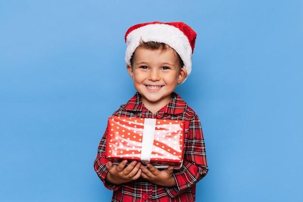 Ein glücklicher kleiner junge im weihnachtspyjama und einem hut mit einer geschenkbox. die studioaufnahme ist auf blauem grund vergoldet. das konzept der ferien.