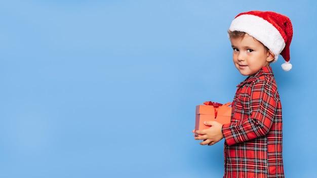 Ein glücklicher kleiner junge im weihnachtspyjama und einem hut mit einer geschenkbox. ein platz für ihren text. studioaufnahme auf blauem hintergrund. das konzept von neujahr und weihnachten.