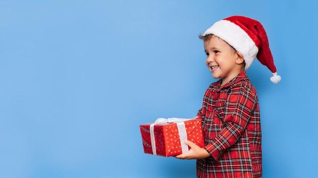 Ein glücklicher kleiner junge im weihnachtspyjama und einem hut mit einer geschenkbox. ein platz für ihren text. studioaufnahme auf blauem hintergrund isoliert. das konzept der ferien.