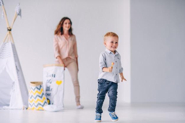 Ein glücklicher kleiner junge mit süßigkeiten in den händen entkommt seiner mutter in einem hellen raum mit baby-wigwam und öko-taschen