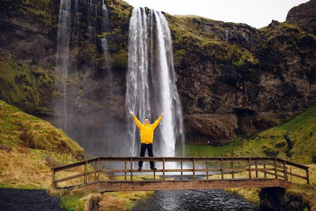 Ein glücklicher mann, der auf dem hintergrund einer isländischen landschaft aufwirft