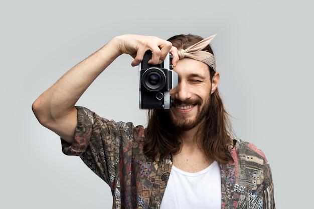Ein glücklicher mann des stilvollen reisefotografen mit langen haaren und einem verband auf seinem kopf fotografiert auf einer filmkamera und lächelt, während er durch die linse einer linse auf einem weißen studiohintergrund schaut