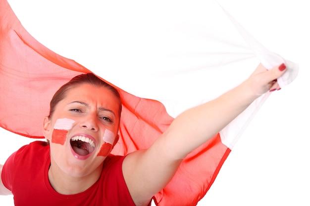 Ein glücklicher polnischer weiblicher fan, der gegen die polnische flagge jubelt