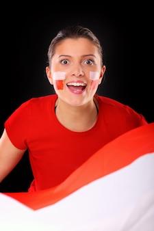 Ein glücklicher polnischer weiblicher fan, der vor schwarzem hintergrund jubelt
