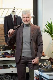 Ein glücklicher reifer mann mit grauen haaren und sportlichem körperbau hält in einem bekleidungsgeschäft zwei schwarze papiertüten mit einkäufen und einen kohlefaserstock. ein männlicher kunde mit bart trägt anzug in einer boutique