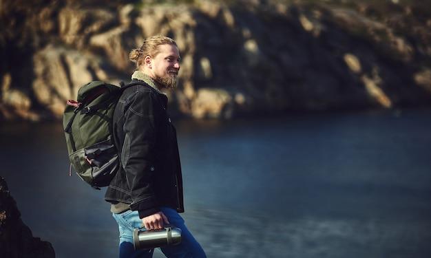 Ein glücklicher reisender, der auf einer klippe steht und die schönheit der natur bewundert.