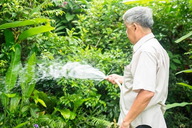 Ein glücklicher und lächelnder alter asiatischer älterer mann gießt pflanzen und blumen für ein hobby nach der pensionierung