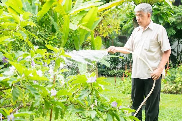 Ein glücklicher und lächelnder asiatischer alter älterer mann gießt pflanzen und blumen für ein hobby nach dem ruhestand in einem haus. konzept eines glücklichen lebensstils und einer guten gesundheit für senioren.
