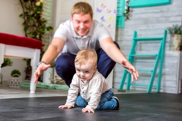 Ein glücklicher vater spielt mit seinem sohn er versucht ein glückliches kind zu fangen, das auf allen vieren krabbelt