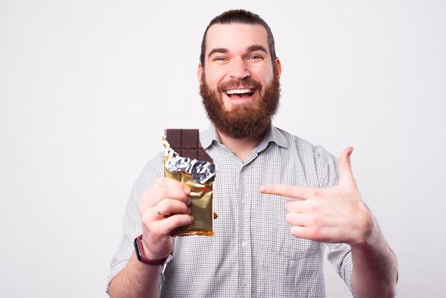 Ein glücklicher zufriedener junger bärtiger mann schaut lächelnd in die kamera und zeigt mit einer großen schokolade darauf, wie er es mag