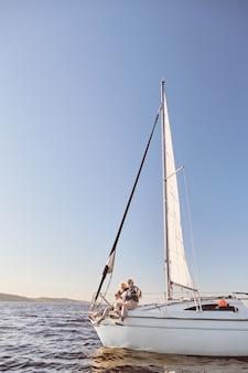 Ein glückliches älteres paar, das an der seite eines segelbootes auf einem ruhigen blauen seemann sitzt, der seine umarmt
